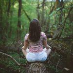 woman sitting in meditation on log
